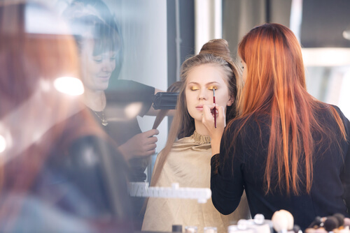 professional make-up artist and hairdresser are working with customer