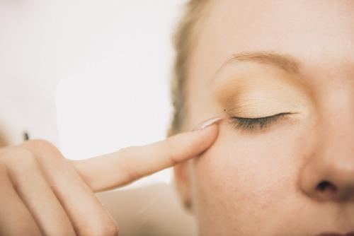 a woman points her finger at her lightly make up eye