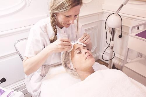 a facial care specialist is doing facial treatment to a customer