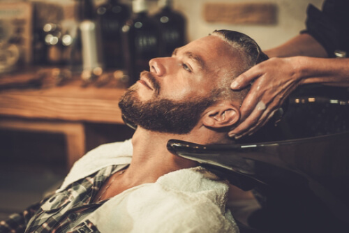 professional hairdresser washing the hair of a man after a haircut