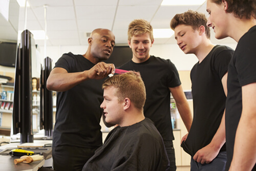 a professional hairdresser demonstrates good practices in front of trainees