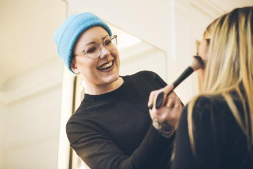 smiled make-up specialist is making up a customer