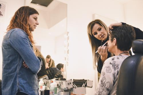 an experienced make-up artist shows good practices to a trainee