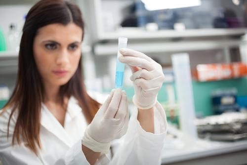 laboratory assistant looks at a tube of light blue liquid