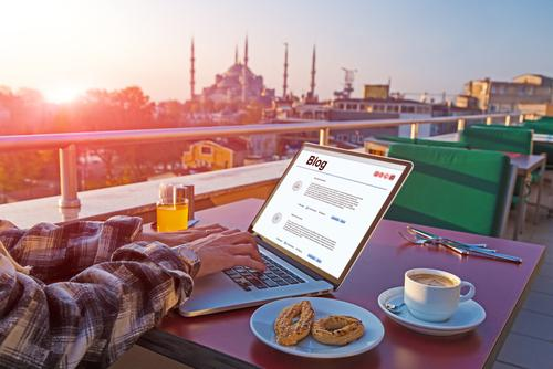 a man filling his blog at sunrise while having breakfast on the terrace