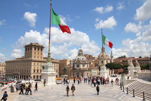A square in Italy with Italian flags.
