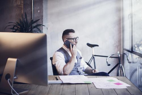 a man is talking on the phone in his office